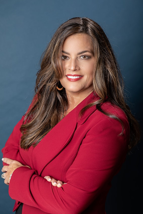 professional headshot of a woman in a red jacket against of a blue backdrop