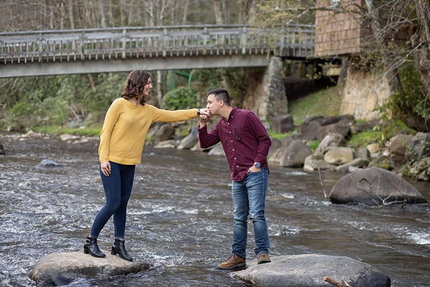 Couple standing on rocks in river at Roan Mountain